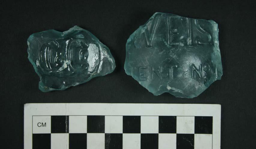 Figure 6.5. Two Budweiser bottle fragments, from Area B of the Pine Level site. (Figure 6.5). One piece has a clear embossed monogram on the base that reads CC&Co.