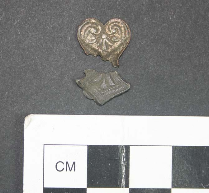 an old-fashioned metal shoelace loop, and what may be two parts of a single delicate heart decoration.
