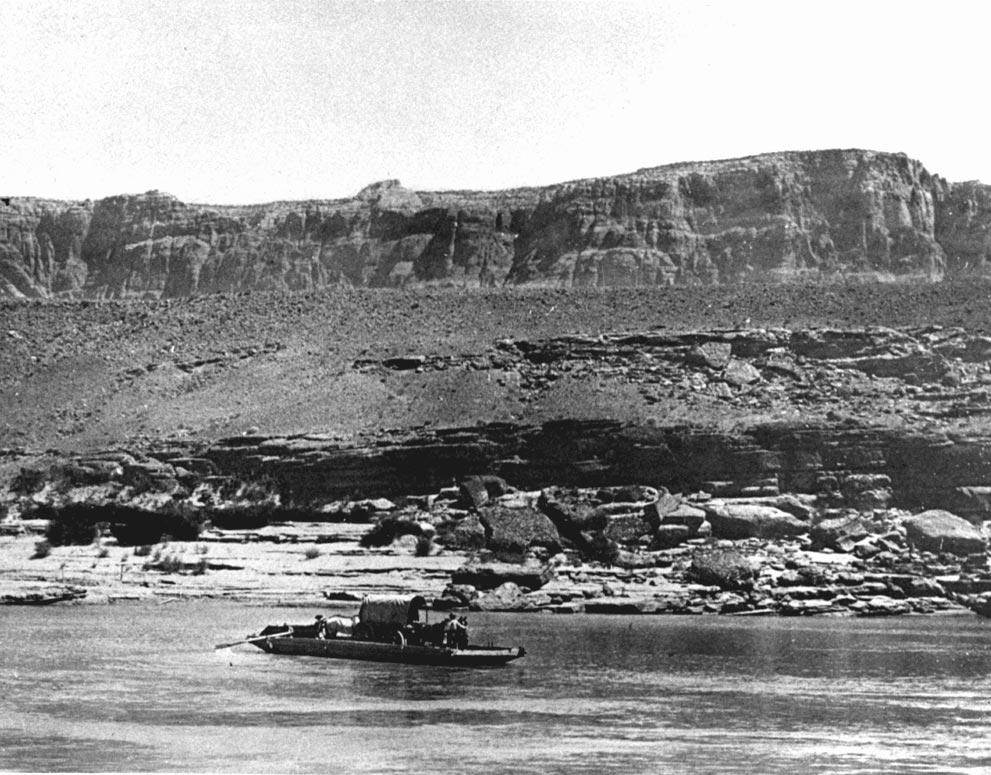 A covered wagon, stock and two men are ferried across the Colorado River on a skow at Lee s Ferry in 1900. Photo F. H.