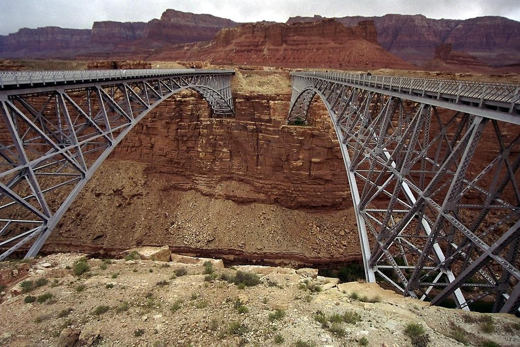Arizona's Historic Navajo Bridge spans Marble Canyon in a graceful silvery arch approximately 470 ft. above the Colorado River. The original 1928 bridge that replaced Lee s Ferry is on the right.