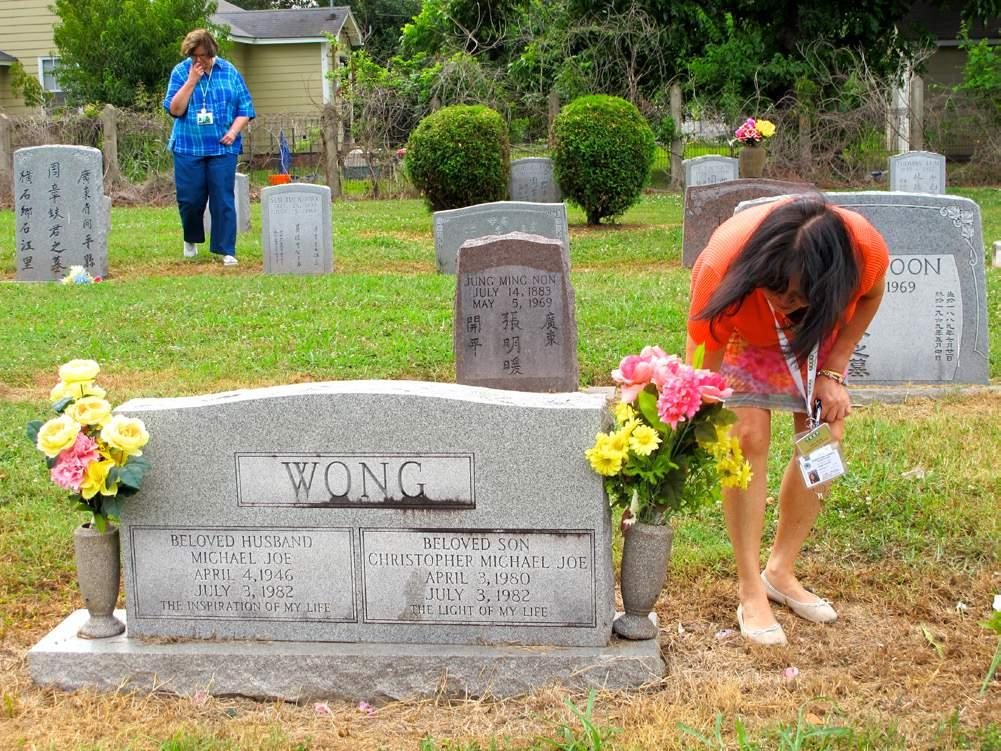 TUESDAY Graveyard caretaker and guest tour guide Catherine Tom Wong adjusts the flowers at a loved ones grave.