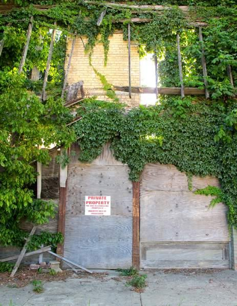 (Left) The Private Property sign on the overgrown barricade is all that remains of Bryant s Grocery today.