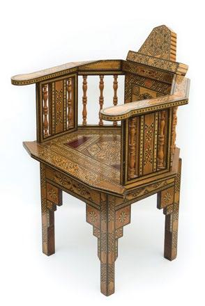 A Syrian Gondola back Mosaic Marquetry Armchair كرسي سوري ذو ذراعني من الطراز العثماني بظهر جندول من اخلشب املطعم بالعاج والصدف of exotic and dyed woods, geometrically decorated overall.