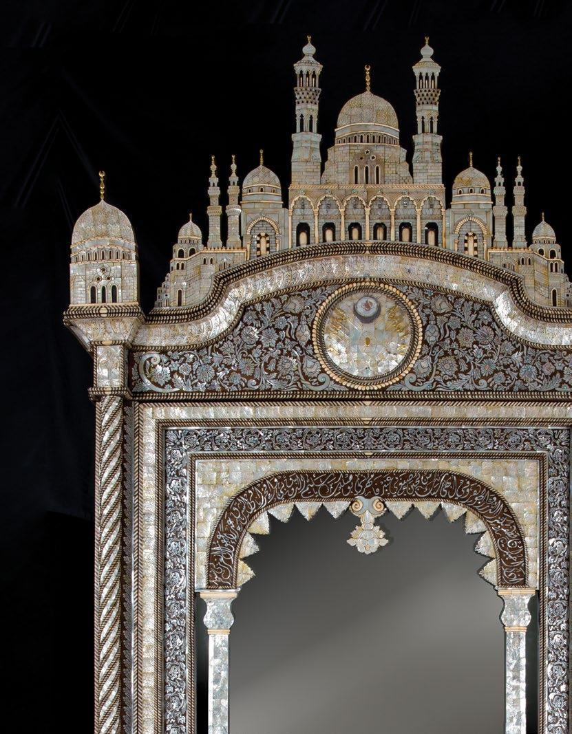The cabinet is surmounted by a mosque shaped pediment of inlaid and carved mother-of-pearl, the arches and windows articulated with ivory inlay and hanging brass mosque lamps (later additions), the