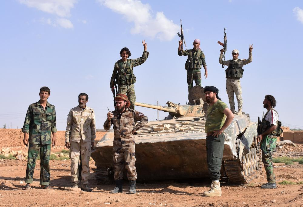 Syrian pro-government forces flash the sign for victory on top of a tank after taking control of the northern Syrian town of Maskanah from the Islamic State on June 5, 2017.