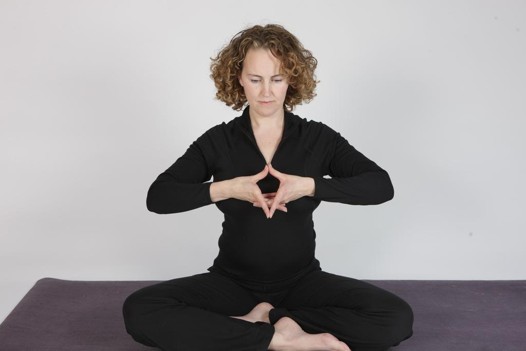 P.5 Yoni Mudra. Begin sitting with your left leg crossed in front of your right leg.