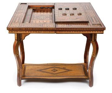A Syrian Mosaic Marquetry Games Table طاولة ألعاب سورية خشبية مطعمة بالعاج والصدف of exotic and dyed woods, geometrically decorated overall, and with rosette-shaped wood and mother-of-pearl-inlay.
